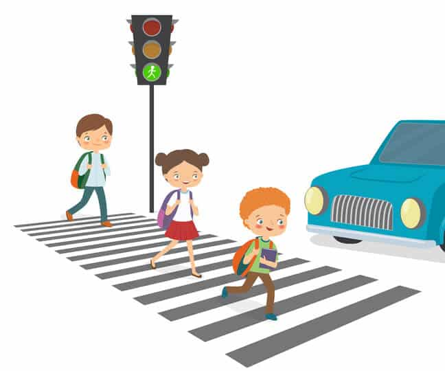 Car brakes while Children cross the road to a green traffic light.